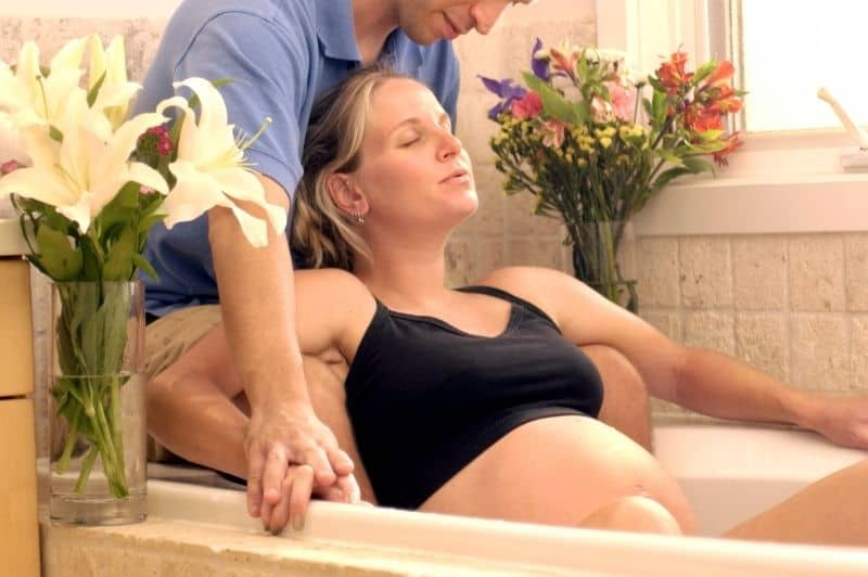 woman giving birth, in labor in bathtub