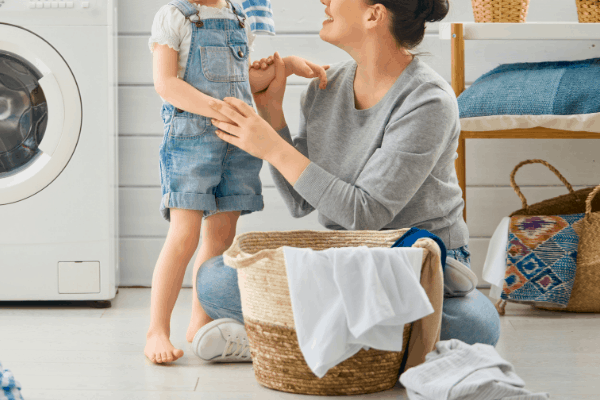 mom at home doing laundry with child